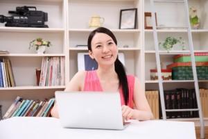 パソコンの前で笑う女性