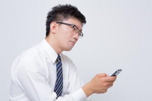 携帯を眺める男性